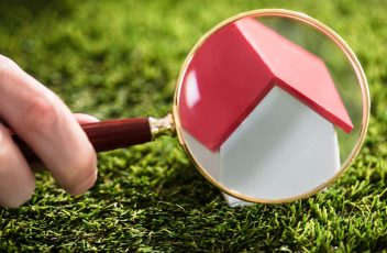 Businessperson Looking At House Model Through Magnifying Glass