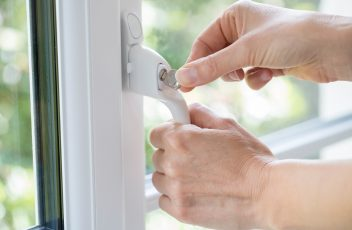 Close Up Of Woman Turning Key In Window Lock
