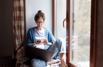 Young woman working from home office. Freelancer using laptop, phone and the Internet.